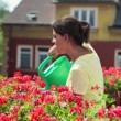 Woman watering flowers on balcony — Stock Video