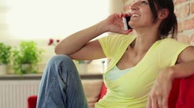 Woman on sofa talking on cellphone — Stock Video