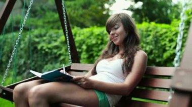 Estudiante en cuaderno de escritura en columpio banco — Vídeo de Stock