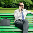 Businessman talking on cellphone in the park — Stock Video