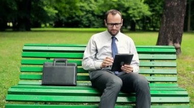 Businessman with tablet in park — Stock Video