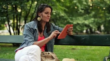 Woman with tablet computer in park — 图库视频影像