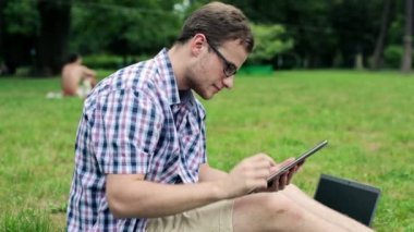 Student with tablet computer in park — Stock Video