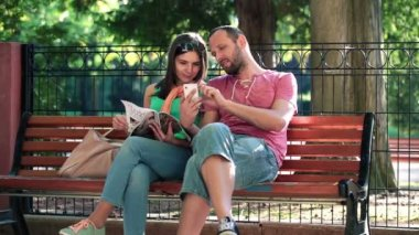 Couple with smartphone sitting on bench — Stock Video