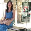 Young woman waiting for bus at bus stop — Stock Video