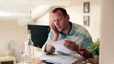 Man med räkningar talar i mobiltelefon — Stockvideo