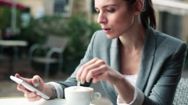 Businesswoman with smartphone in cafe — Stock Video