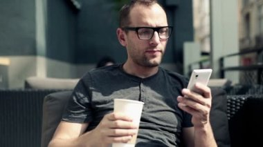 Man sending sms, texting and drinking coffee — Stock Video