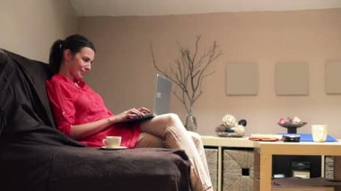Woman with laptop on sofa — 图库视频影像