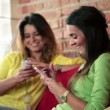 Girlfriends with smartphone on sofa — Stock Video