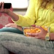 Stock Video: Girlfriends eating chips and watching tv
