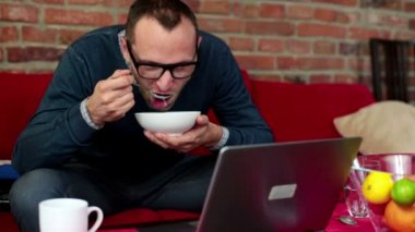 Man with laptop eating soup — Stock Video