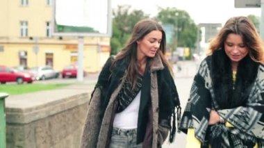 Young happy girlfriends walking in city — Stock Video