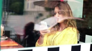 Woman talking on cellphone and drinking cafe latte — Stock Video