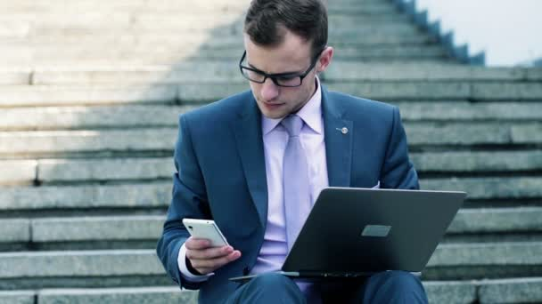 Homme d'affaires avec le smartphone et l'ordinateur portable — Vidéo