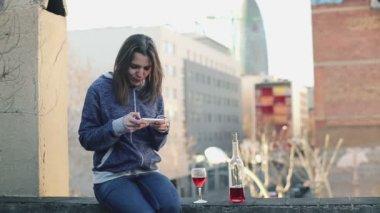 şarap içmek ve akıllı telefon kullanan kadın — Stok video