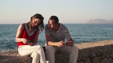 Couple with smartphone by sea — Stock Video