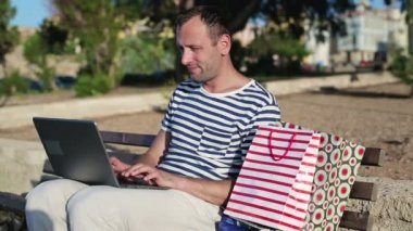 Man with laptop and shopping bags — Stock Video