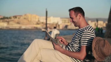 Man chatting on tablet by sea — Stockvideo