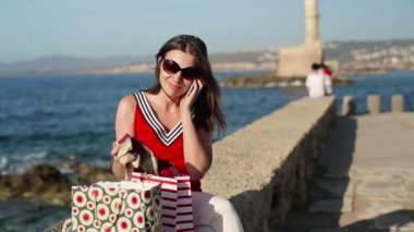 Woman talking on cellphone and checking bags — Vídeo de stock
