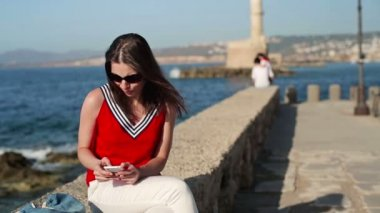 Woman with smartphone sitting by sea — Vídeo stock