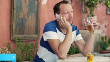 Man talking on cellphone and drink beer — Stock Video