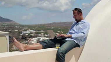 Man working on laptop on terrace — Vídeo de stock
