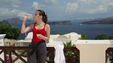Woman drinking water on terrace — Vidéo