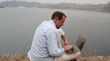 Mann mit modernen laptop am meer — Stockvideo