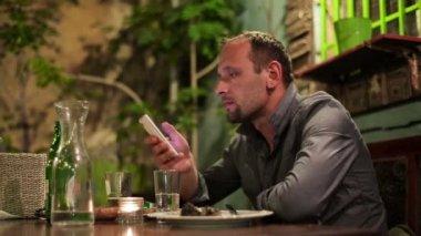 Man using smartphone in bar — Stock Video