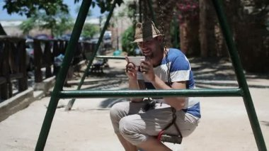 Man on swing with smartphone — Stock Video