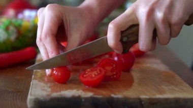 Slicing cherry tomatoes on chopping board — Stock Video