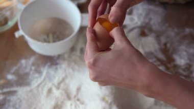 Hands cracking egg over flour — Stock Video