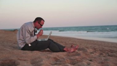 Frustrated businessman with laptop on beach — Stock Video