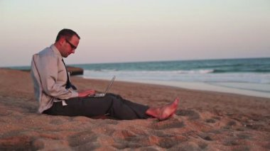 Businessman working on laptop on beach — Stock Video
