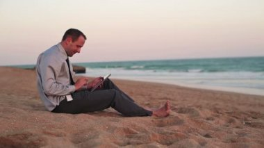 Businessman on tablet computer on beach — Stok video