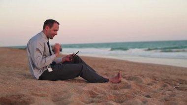 бизнесмен с планшетного компьютера на пляже — Стоковое видео