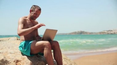 Man finishing work on laptop on beach — Stock Video