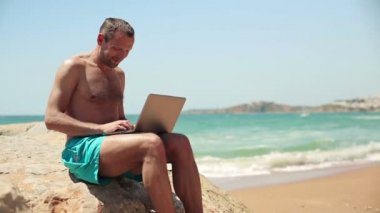 Man working on laptop on beach — Stock Video