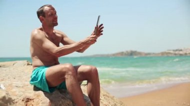 Man taking photo with tablet on beach — Stock Video