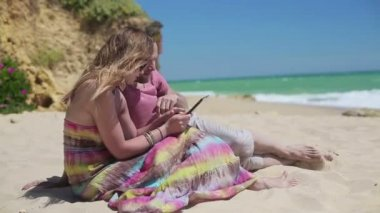 Couple with tablet on beach — Stock Video