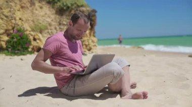 Man working on laptop on beach — Stock Video