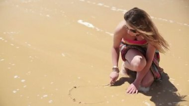 Woman drawing heart in sand — Stock Video