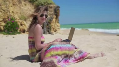 Woman working on laptop on beach — Stock Video