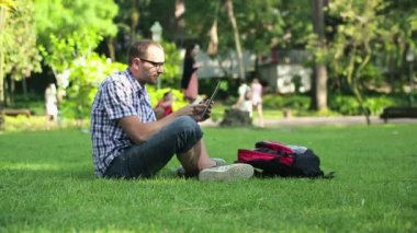 Student using smartphone and tablet in the park — Vídeo de Stock