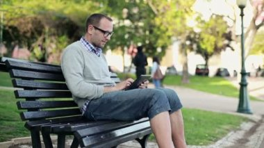 Happy man with tablet in the city park — Stock Video
