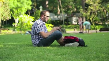 Student using tablet computer in the park — Stock Video