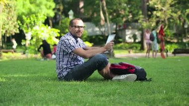 Student with tablet computer in the park — Stock video