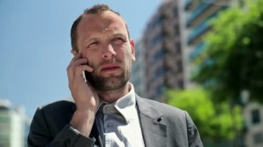 Businessman talking on mobile phone in city — Vídeo Stock