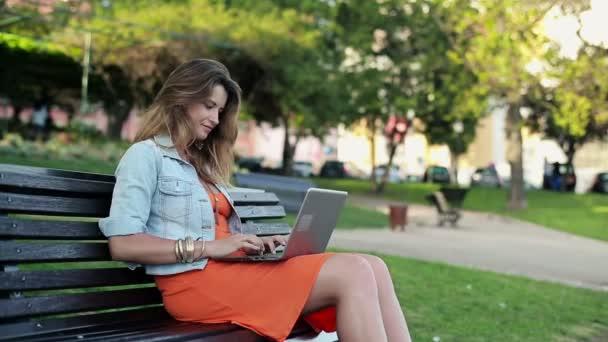 Mujer con el portátil en el parque de la ciudad — Vídeo de stock